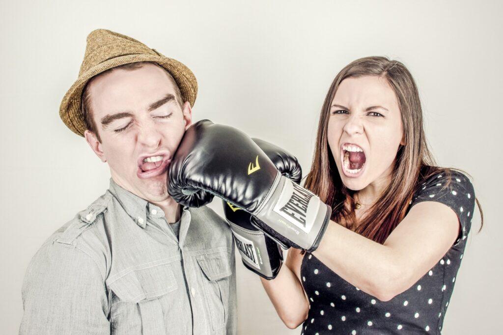 Vrouw slaat een man met boxhandschoen